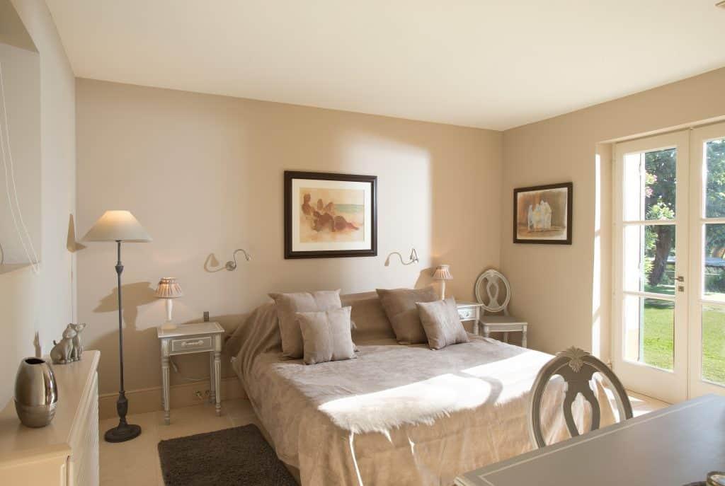 chambre double aux tons beige de la maison de vacances donnant sur le jardin verdoyant, sur la vue mer, la piscine miroir et son gazebo